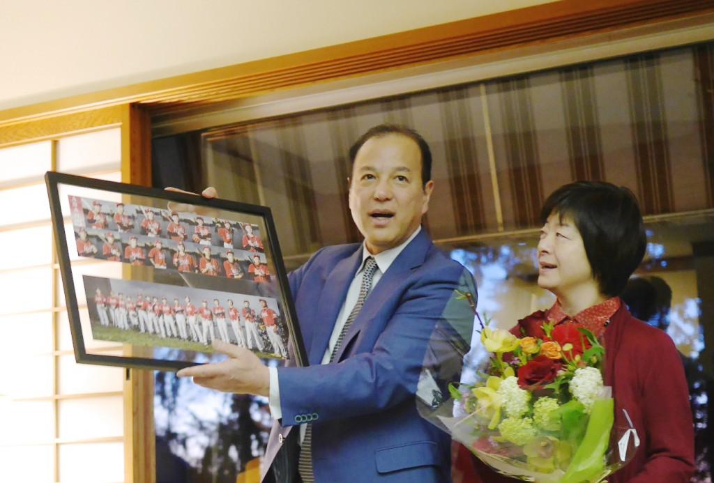 チームよりポスターとチームより壮行会のお礼にポスターと花束のプレゼントを受け取った岡田総領事と寧子夫人花束のプレゼントを受け取った岡田総領事と寧子夫人