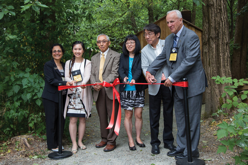 Cutting the ribbon for the re-opening event of the Ofuro (Japanese bath) exhibit at Burnaby Village Museum.