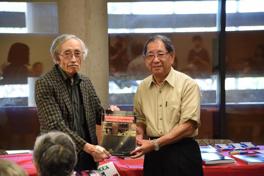 6月4日出版記念会: 証言者、ウォルター・松田氏(右)に担当の編集委員、鹿毛達雄から本を贈呈。 写真提供: ジョン・遠藤・グリーナウェイ